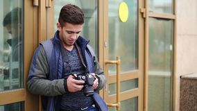 Young guy looks at the digital camera while in the city stock footage