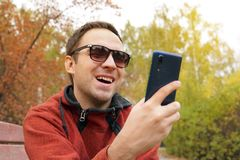Young guy looks at the phone screen laughing and rejoicing. communication communication of people through the network royalty free stock photography