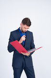 Young guy looks in the red folder Royalty Free Stock Photos