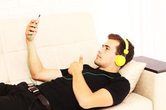 Young guy is lying on the bed, listening to music and making selfie on his phone. Copy space Stock Images