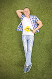 Young guy lying on grass and holding flowers Stock Photo