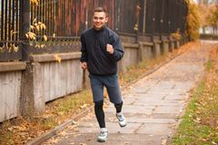 A young guy makes a light jog in the autumn park. The concept of sport. A young sports guy, of European appearance, dressed in sports clothes, makes a light jog Royalty Free Stock Image