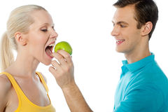 Young guy making her girlfriend eat an apple. Young guy making her pretty girlfriend eat an apple. Healthy couple Royalty Free Stock Image
