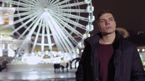 Young guy meets with friend near ferris wheel. Young guys stands in the amusement park and waits his friend near the ferris wheel. Handsome student is looking stock video footage