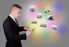 Young guy with mobile phone and icons. Royalty Free Stock Image
