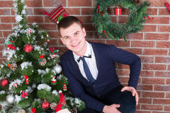 Young guy next to a Christmas tree Royalty Free Stock Photo