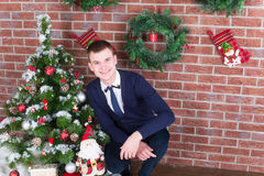 Young guy next to a Christmas tree Royalty Free Stock Photography