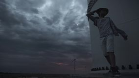 A young guy next to the wind turbines, produce ecological energy. The concept of environmental pollution, new. Technologies of alternative energy. General plan stock video footage