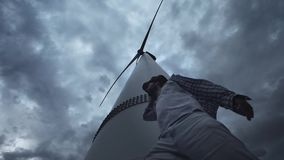 A young guy next to the wind turbines, produce ecological energy. The concept of environmental pollution, new