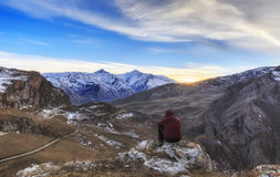 Young guy overlooks the mountainous surroundings of the village stock images