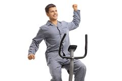 Young guy in pajams stretching on an exercise bike stock image