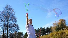 A young guy in the park makes big soap bubbles. Holiday and outdoor entertainment. Holiday and outdoor entertainment. A young guy in the park makes big soap stock video footage
