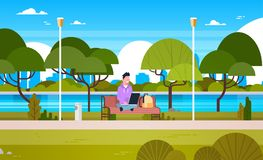 Young Guy In Park Using Laptop Computer Outdoors Sitting On Bench. Flat Vector Illustration Royalty Free Stock Photography