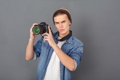 Young male photographer in jeans jacket studio isolated on grey holding camera up royalty free stock photography