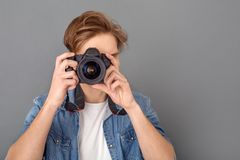 Young male photographer in jeans jacket studio isolated on grey taking photos close-up. Young guy photographer wearing jeans jacket studio isolated on grey wall Royalty Free Stock Images