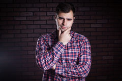 Young guy in a plaid shirt frowns Stock Image