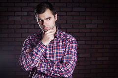 Young guy in a plaid shirt frowns Stock Photos