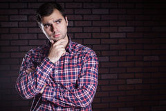 Young guy in a plaid shirt frowns Royalty Free Stock Photo