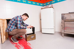 Young guy in plaid shirt squatting and opening the safe trying t. O get out of the kitchen with a bloody floor, escape the room game concept royalty free stock photos
