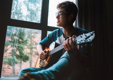 Young guy plaing on guitar and sits near the window Royalty Free Stock Images