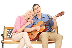 Young guy playing guitar to his girlfriend Stock Photography