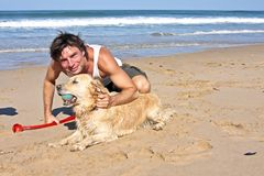 Young guy playing with his dog. At the beach Royalty Free Stock Image