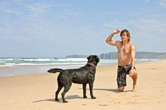 Young guy playing with his dog. At the beach Stock Photo