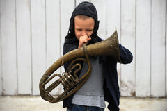 A young guy plays with a musical instrument. And a prize for races on a rural farmstead in a hot summer Stock Images