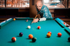 Young guy plays pool billiard Royalty Free Stock Photography