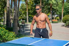 A young guy plays table tennis without shirts in a park on a background of palms in a tourist city in the summer. A young man plays table tennis without shirts stock image