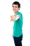 Young guy pointing you. Out with his stretched left arm. All on white background Stock Photography