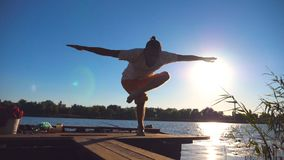 Young guy practicing yoga moves and positions on edge of wooden jetty at lake on sunny day. Sporty man training at stock video footage