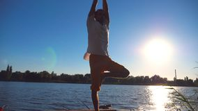 Young guy practicing yoga position on the edge of wooden jetty at lake on summer day. Sporty man doing exercise near. Lake with sunlight at background. Healthy stock footage