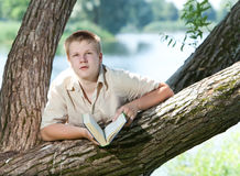 Young guy prepare for lessons in park Stock Photo
