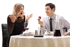 Young guy proposing to his girlfriend at a restaurant table Royalty Free Stock Photography