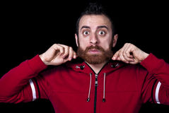 Young guy pulls his long red beard royalty free stock photography