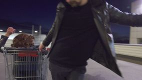Young guy pushes another guy dressed like woman sitting in shopping cart. stock footage