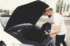 A young guy put luggage in the trunk of their electric car. It is located in front of the machine. It`s a suitcase Stock Photography