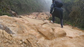 Young guy in raincoat jumping and jogging on rocky trail during travel. Hiking man with backpack running in stone ground stock footage