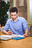 Young guy read a newspaper and holding phone in the Italian styl royalty free stock photography