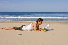 Young guy reading at the beach Stock Photo