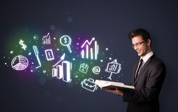 Young guy reading a book with business icons Stock Photo