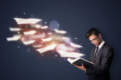 Young guy reading a book with flying sheets coming out of the bo Stock Photo