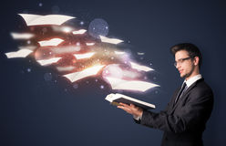 Young guy reading a book with flying sheets coming out of the bo. Ok, magical reading concept Stock Images