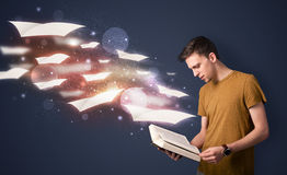 Young guy reading a book with flying sheets coming out of the bo. Ok, magical reading concept Stock Image