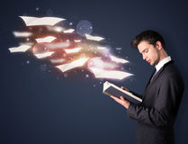 Young guy reading a book with flying sheets coming out of the bo. Ok, magical reading concept Stock Photography