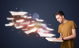 Young guy reading a book with flying sheets coming out of the bo Stock Photography