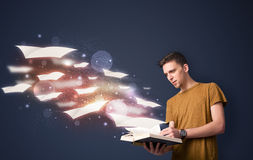 Young guy reading a book with flying sheets coming out of the bo. Ok, magical reading concept Stock Photo