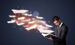 Young guy reading a book with flying sheets coming out of the bo. Ok, magical reading concept Royalty Free Stock Image