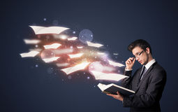 Young guy reading a book with flying sheets coming out of the bo. Ok, magical reading concept Royalty Free Stock Photos